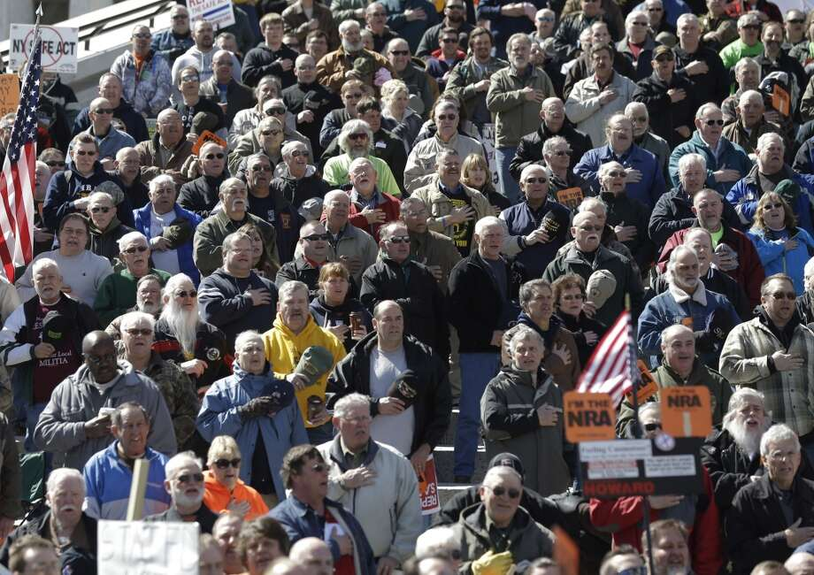 Gun rights activists recite the Pledge of Allegiance during a rally at the Empire State Plaza on Tuesday, April 1, 2014, in Albany, N.Y. The activists are seeking a repeal of a 2013 state law that outlawed the sales of some popular guns like the AR-15. The law championed by New York Gov. Andrew Cuomo has been criticized as unconstitutional by some gun rights activists. (AP Photo/Mike Groll) Photo: Mike Groll, AP