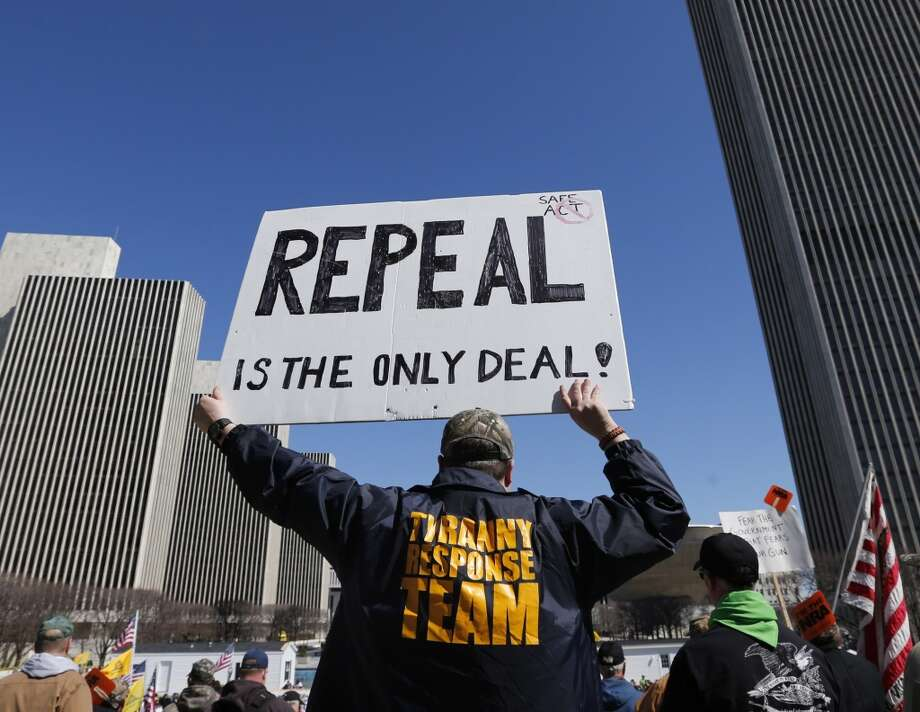A gun rights activist holds a sign during a rally at the Empire State Plaza on Tuesday, April 1, 2014, in Albany, N.Y. Activists are seeking a repeal of a 2013 state law that outlawed the sales of some popular guns like the AR-15. The law championed by New York Gov. Andrew Cuomo has been criticized as unconstitutional by some gun rights activists. (AP Photo/Mike Groll) Photo: Mike Groll, AP