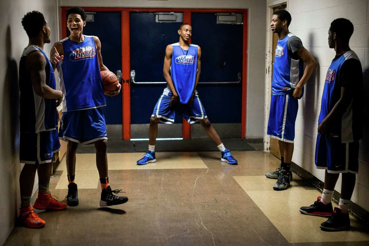 David Crisp, left, and Dejounte Murray, center left, crack jokes in a hallway outside of the gym amid other members of the Rainier Beach High School boys basketball team before a pep rally Monday, March 31, 2014, at Rainier Beach High School in Seattle. On April 2, the team will travel to New York to compete against other top teams from across the country in the DICK'S Sporting Goods National High School Tournament.