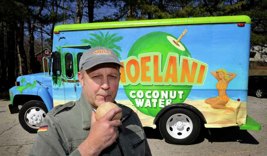 Ed Hartz of Sandy Hook sips some coconut milk in front of his delivery truck, Tuesday, April 1, 2014. He os the owner of Noelani Coconut Company, a coconut milk delivery business. Photo: Carol Kaliff / The News-Times