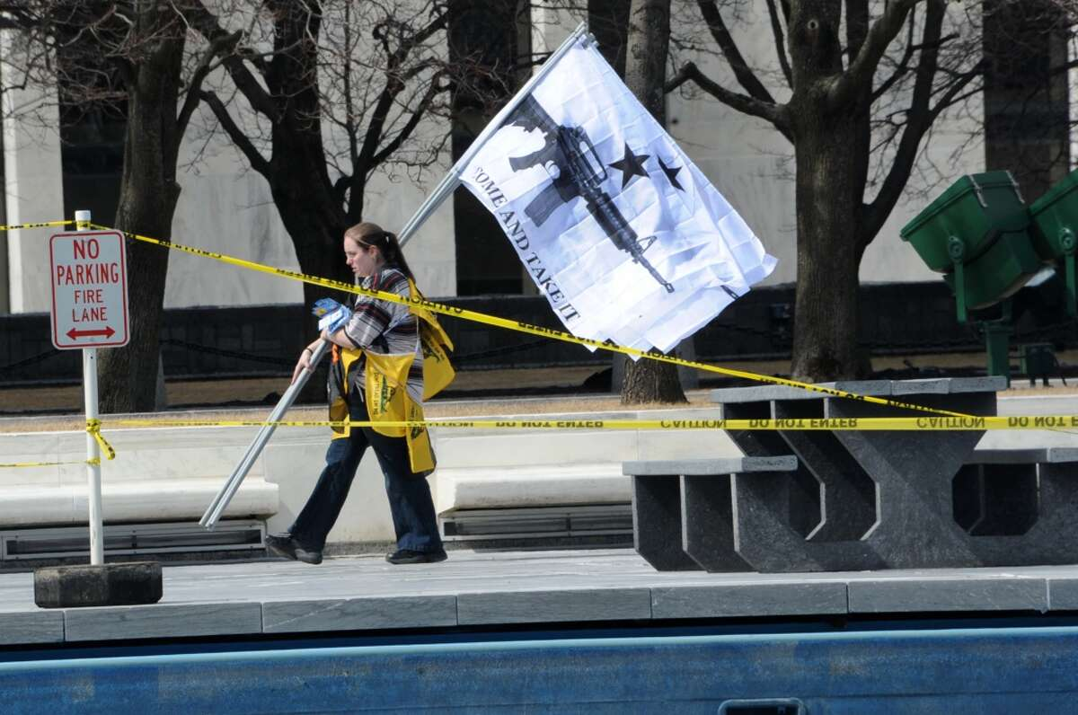 """A woman is seen carrying flags reading """"Come and Take It"""" as second amendment advocates rally against the NY SAFE Act at the Empire State Plaza Tuesday April 1, 2014 in Albany, N.Y. (Lori Van Buren / Times Union)"""