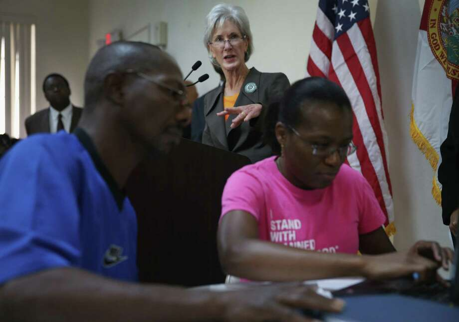 U.S. Secretary of Health and Human Services Kathleen Sebelius watches as people sign up for insurance under the Affordable Care Act at an event held Saturday at a church in Miami, ahead of Monday's deadline. Photo: Getty Images / 2014 Getty Images