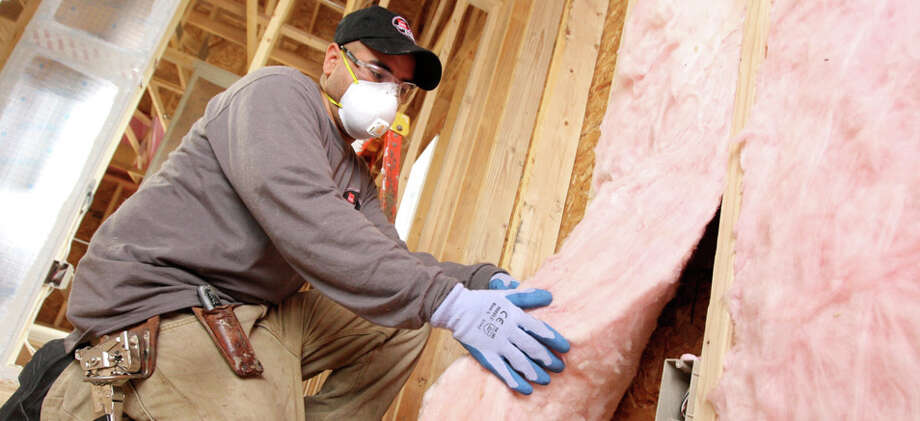 An employee with Installed Building Products works to install insulation. The Ohio-based company has acquired Danbury's U.S. Insulation Corp., adding to its insulation services portfolio. Photo: Contributed Photo / Danbury News-Times Contributed