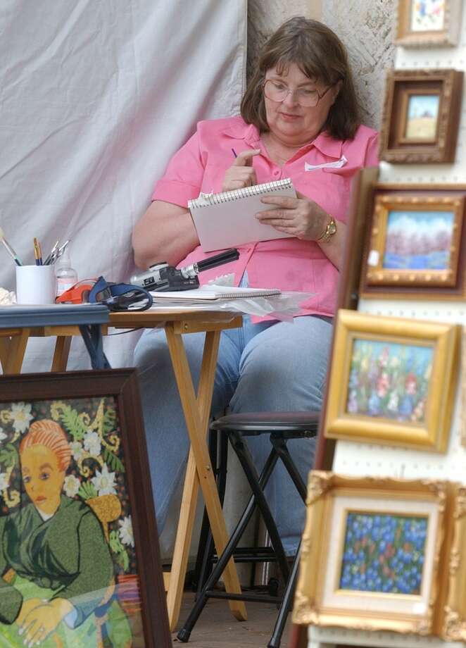 Aletha Lane paints a watercolor as she waits for customers at the Starving Artist Art  Show in 2003. Photo: Express-News, File
