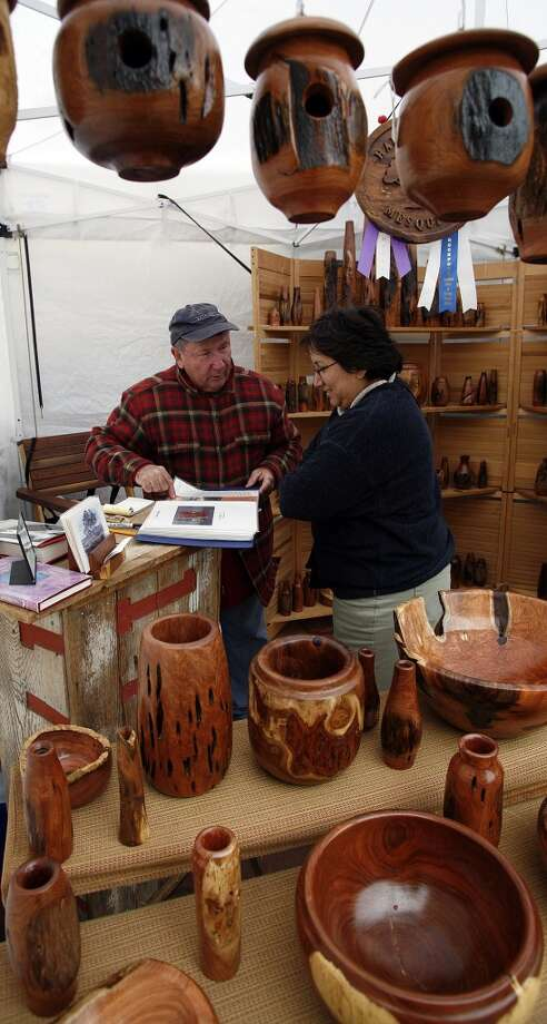 Curtis Alston Laudermilk (left) shows samples of his handcrafted mesquite art to Rosie Reyes during the Starving Artist Art Show in 2007. Photo: J. Michael Short, Express-News