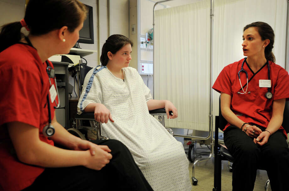 Theater student Shannon Galgay, center, plays the role of a terminally ill patient in a simulation with nursing students Megan Marbach, left, and Lauren Kemple at Fairfield University's School of Nursing on Tuesday, April 1, 2014. Photo: Brian A. Pounds / Connecticut Post