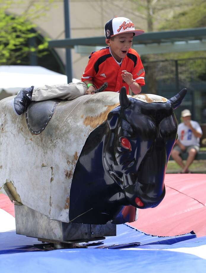Lucas Wilson 7, of Humble rides the mechanical bull at the 13th Annual Opening Day Street Festival. Photo: Karen Warren, Houston Chronicle