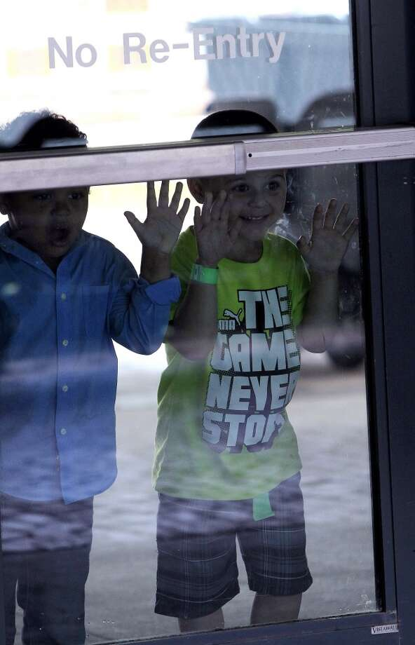 Zack Ovalle, 4, and his cousin, Gabriel Ovalle, 3, of San Antonio peek into the door as they enjoy the festivities at the 13th Annual Opening Day Street Festival on Crawford Street. Photo: Karen Warren, Houston Chronicle