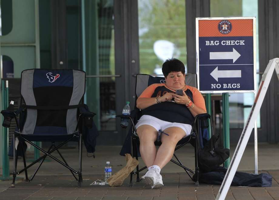Elva Marroquin sits in her chair, the first in line at the Crawford gate at noon before the start of the Astros-Yankees game. Photo: Karen Warren, Houston Chronicle