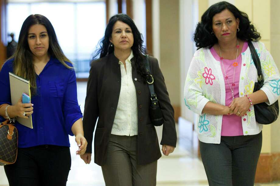 Ana Lilia Trujillo, center, walks to the courtroom following a break in her trial Tuesday, April 1, 2014, in Houston.  Photo: Brett Coomer, Houston Chronicle / © 2014 Houston Chronicle