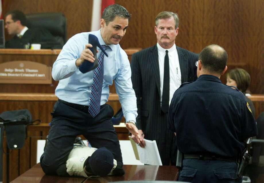 Prosecutor John Jordan does a crime scene demonstration, using a dummy, during the trial against Ana Lilia Trujillo  Tuesday, April 1, 2014, in Houston. Trujillo, 45, is charged with murder, accused of killing her 59-year-old boyfriend, Alf Stefan Andersson with the heel of a stiletto shoe, at his Museum District high-rise condominium in June 2013. Defense attorney Jack Carroll, center, and crime scene investigator Christopher Duncan are shown in the background. Photo: Brett Coomer, Houston Chronicle / © 2014 Houston Chronicle
