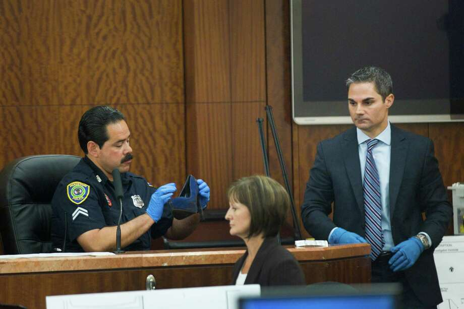 Houston police officer Ernest Aguilera examines a stiletto shoe entered into evidence by prosecutor John Jordan, right, on Tuesday, April 1, 2014. Photo: Brett Coomer, Associated Press / Houston Chronicle