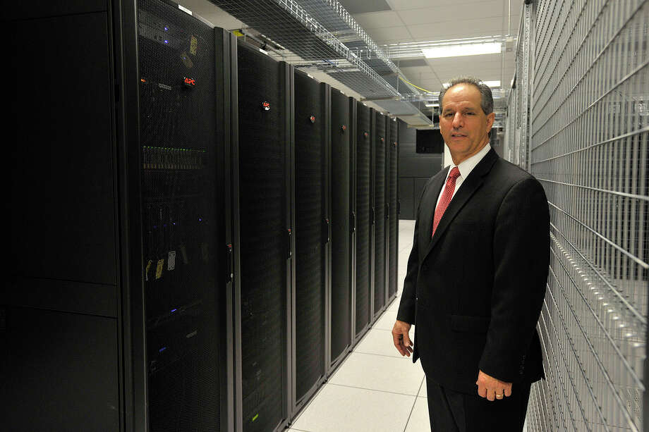President and CEO Michael Boccardi poses next to a few of his customer's cabinets in the data center at Cervalis' data facility in Norwalk, Conn., on Tuesday, April 1, 2014. Cervalis provides IT infastructure solutions throughout its four data centers in the tri-state area, two of which are in lower Fairfield County. Photo: Jason Rearick / Stamford Advocate
