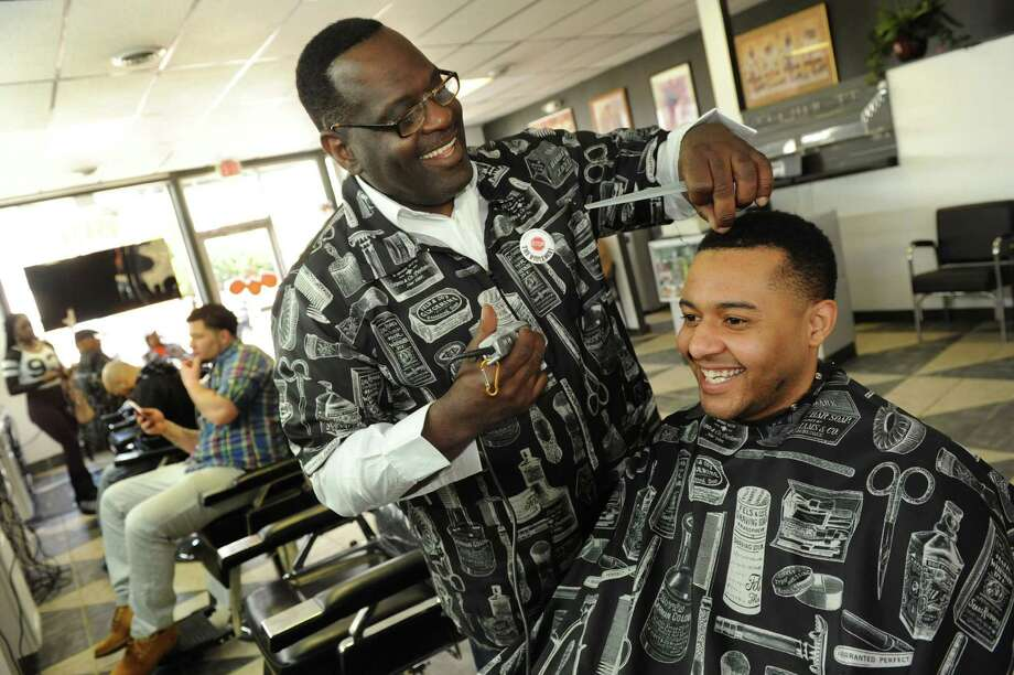 "Manager Robert ""Mr. O"" Odom, left, teases when he finds a gray hair on Claude ""Phrenchy"" Roach III, manger at Love-Cuts 1, on Tuesday, April 1, 2014, at Love-Cuts 2 Barber Shop in Albany, N.Y. (Cindy Schultz / Times Union) Photo: Cindy Schultz / 00026099A"
