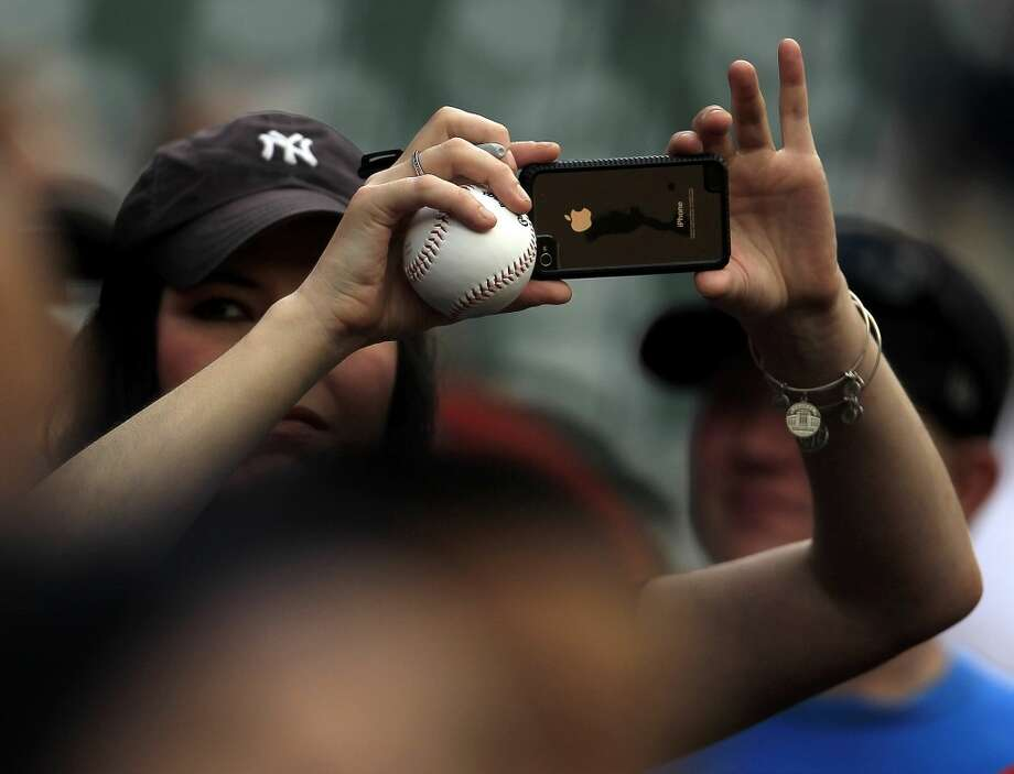 A New York Yankees fan shoots photos from the stands before the game. Photo: Karen Warren, Houston Chronicle