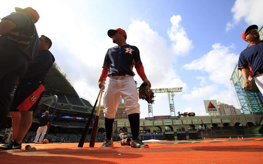 Jose Altuve picks up his bats and glove during batting practice. Photo: Karen Warren, Houston Chronicle