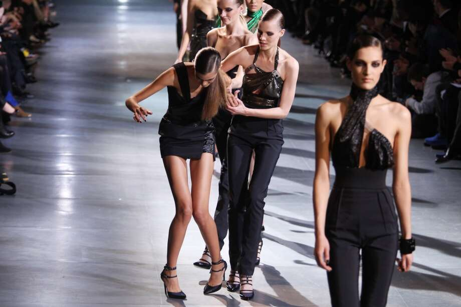 A model is assisted by other models after tripping on the runway during the Anthony Vaccarello Ready-To-Wear Fall/Winter 2012 show as part of Paris Fashion Week at Docks en Seine on February 28, 2012 in Paris, France. Photo: Antonio De Moraes Barros Filho, WireImage
