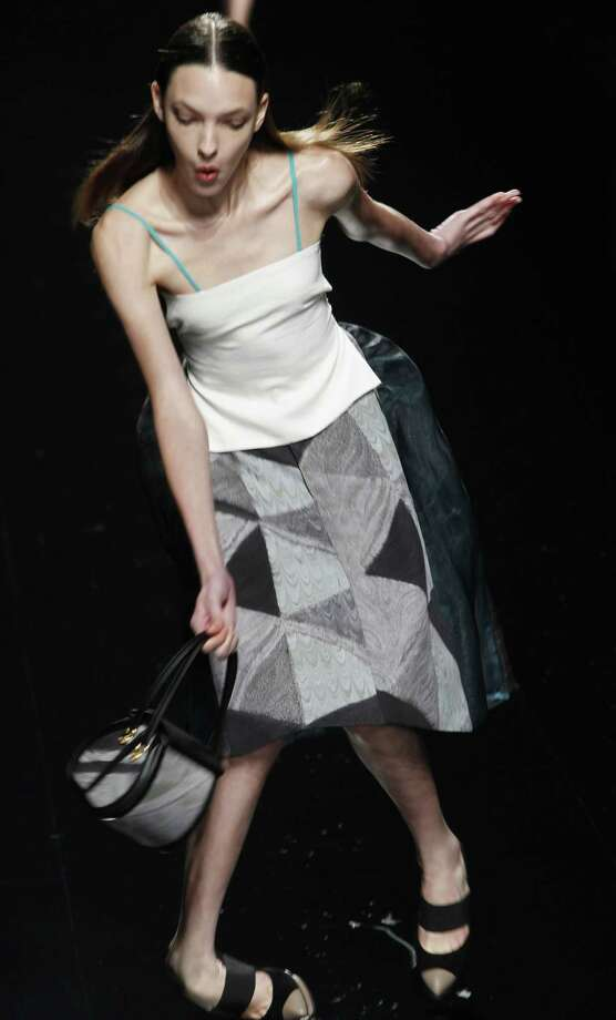 In this Oct. 20, 2011 file photo, a model loses her balance while modeling the 2012 spring/summer collection by Araisara during Fashion Week in Tokyo. Photo: Koji Sasahara, Associated Press / AP2011