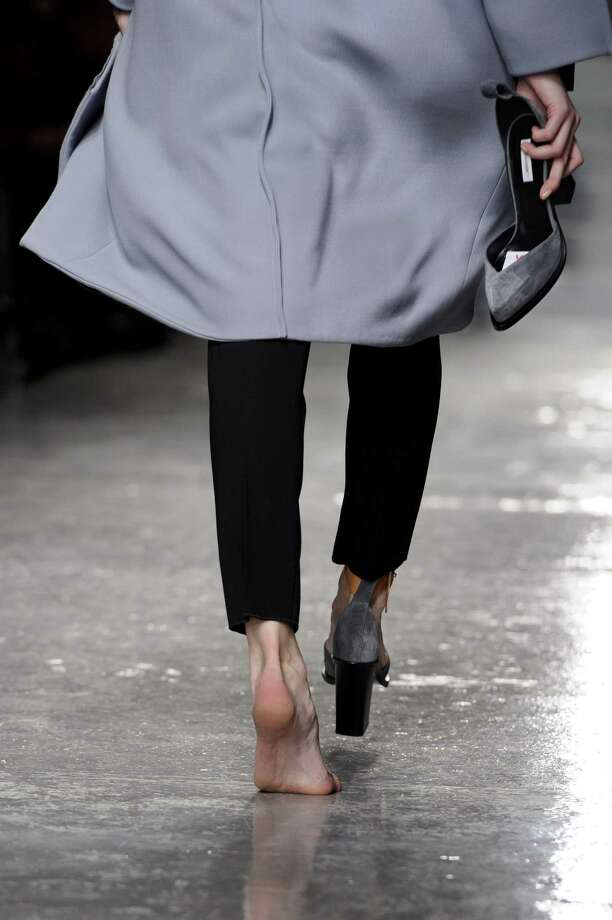 In this Feb. 22, 2011 file photo, a model walks the runway holding her shoe after losing it during the showing of the Aquascutum collection during Fashion Week in London. Photo: Jonathan Short, Associated Press / AP2011 This content is intended for editorial use only. For other uses, additional clearances may be required.
