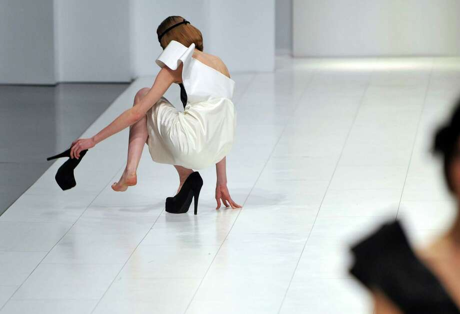 A model takes her shoe off after she fell while displaying a dress from the ready to wear collection by popular Romanian fashion designer Andreea Tincu & Sence during the Ukrainian Fashion Week show in Kiev on March 12, 2010. Photo: SERGEI SUPINSKY, AFP/Getty Images