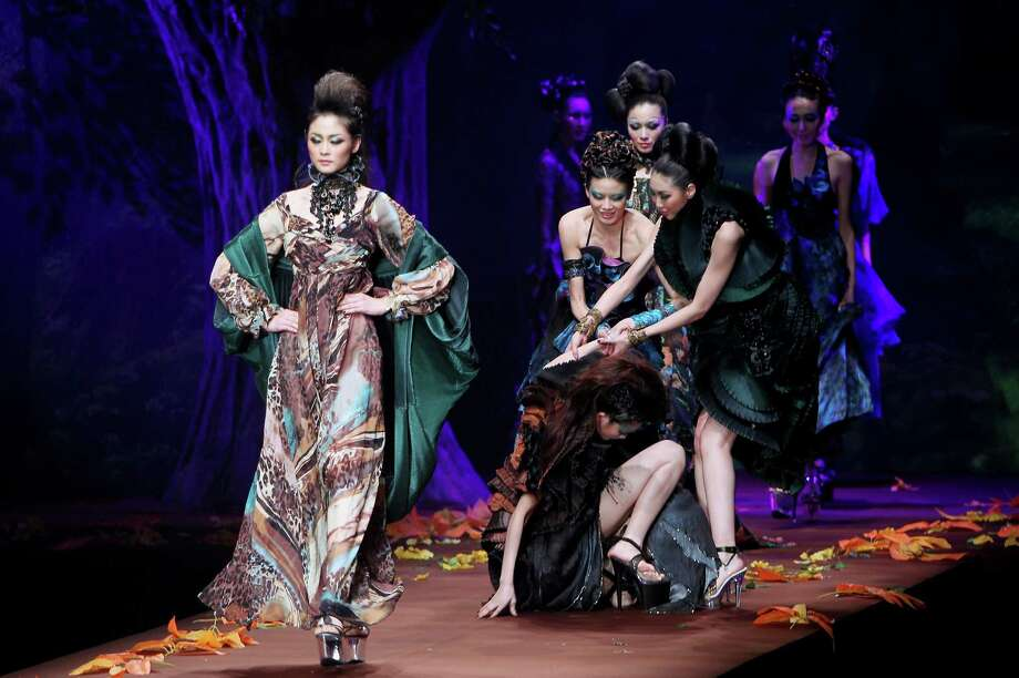 A model is helped after falling down on the runway during AsahiKASEI Prize Zhang Yichao Show at China Fashion Week on March 29, 2010 in Beijing, China. Photo: Feng Li, Getty Images / 2010 Getty Images
