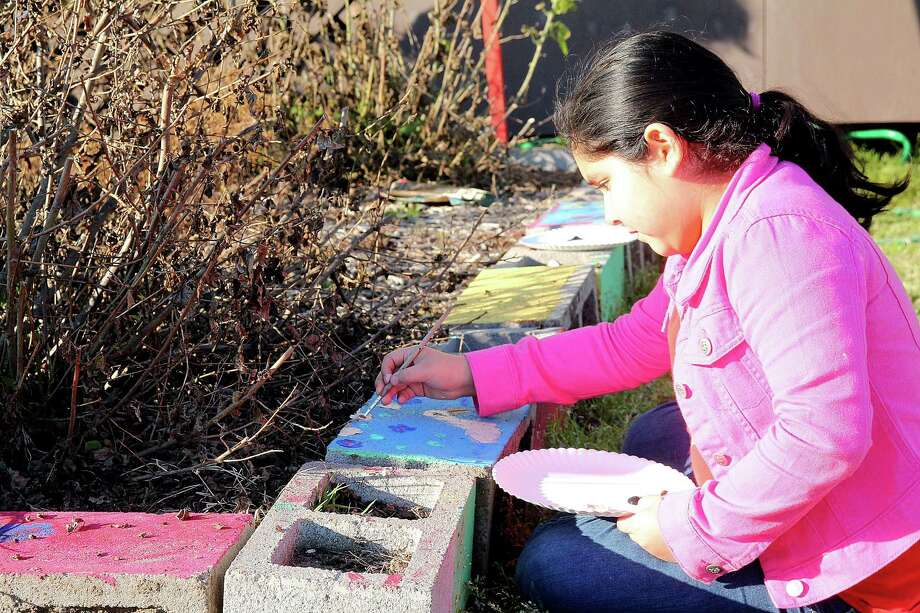 Gissell Perez decorates the raised bed. She and other Richey Elementary pupils worked under the direction of Artist Boat teacher Tim Berk to build their outdoor habitat. Gissell Perez decorates the raised bed. She and other Richey Elementary pupils worked under the direction of Artist Boat teacher Tim Berk to build their outdoor habitat. Photo: Pin Lim, Freelance / Copyright Pin Lim.