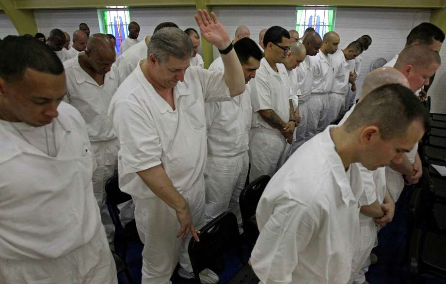 Prisoners at the Texas Department of Criminal Justice's Darrington Unit, 59 Darrington Unit Road, pray during a Convocation ceremony    Monday, Aug. 29, 2011, in Rosharon. Texas prison officials, Houston lawmakers and representatives of Southwestern Baptist Theological Seminary celebrated the opening of the state's first 4-year prison seminary program.   The nondenominational program, sponsored by the TDCJ, Southwestern Baptist Theological Seminary, Southern Baptists of Texas Convention and the Heart of Texas Foundation, will train inmates who are serving lengthy sentences to become ministers. Once they graduate from the program, the inmates will go to other Texas prison facilities where they will minister to their fellow offenders.  ( Melissa Phillip / Houston Chronicle ) Photo: Melissa Phillip, Staff / © 2011 Houston Chronicle
