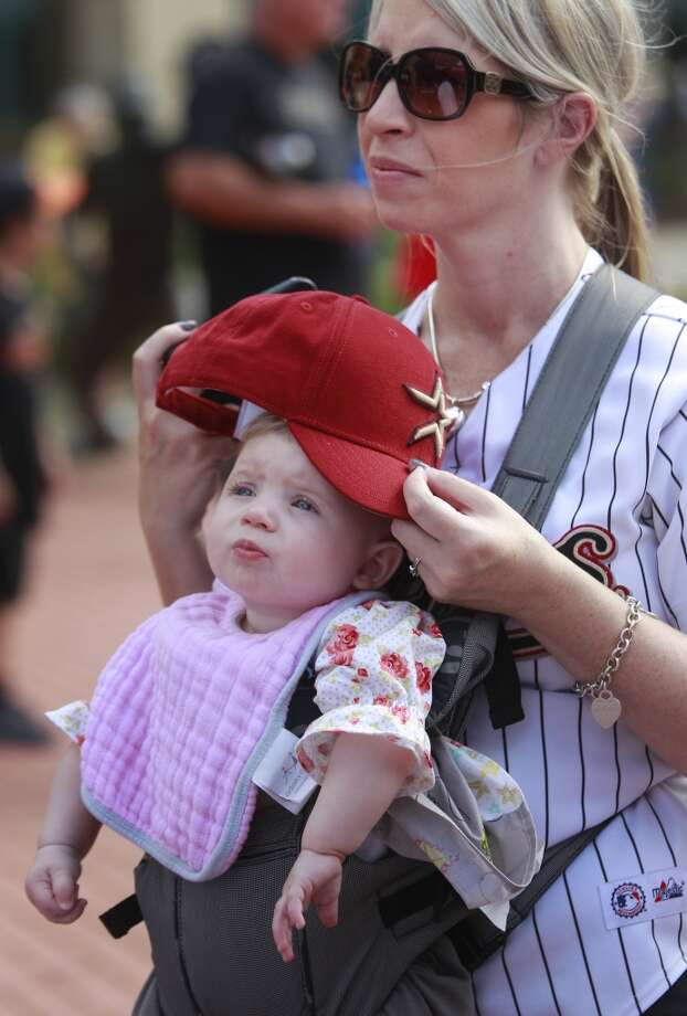 Michelle Carnes of Spring shields her 7-month -old daughter, Kinzley, with an Astros hat as they attend the 13th Annual Street Festival. Photo: Melissa Phillip, Houston Chronicle