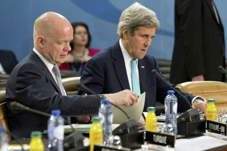 """U.S. Secretary of State John Kerry (right), at a NATO-Ukraine Commission meeting in Brussels, said the U.S. commitment to NATO alliance members' security is """"unwavering."""" Photo: Jacquelyn Martin / Getty Images / AFP"""