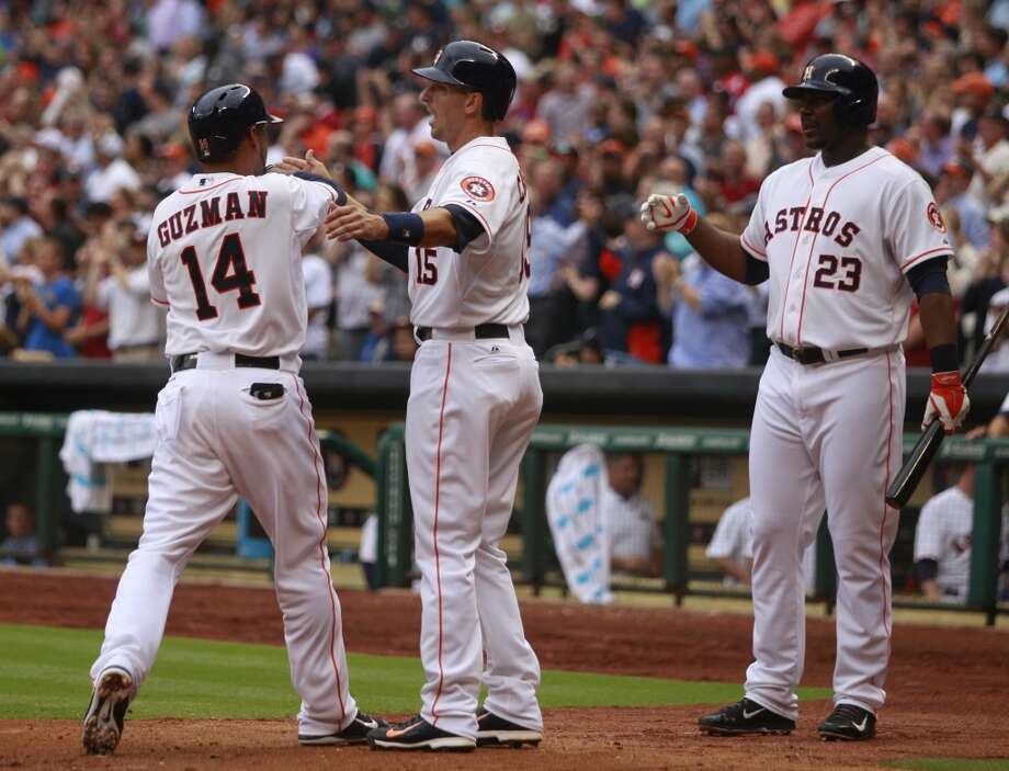 Jesus Guzman of the Astros is greeted by teammates at home plate after hitting a home run against the Yankees. Photo: Melissa Phillip, Houston Chronicle