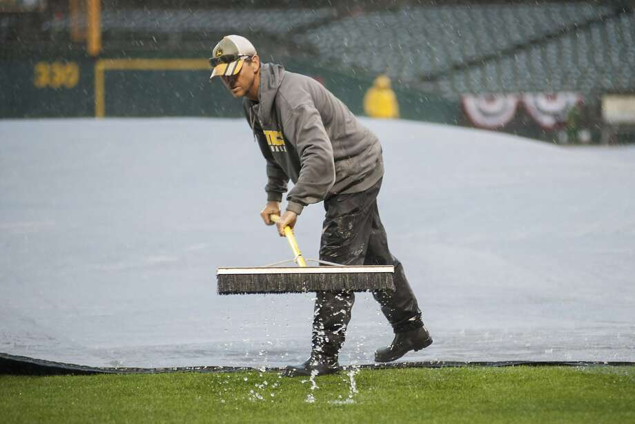 A member of the Oakland Athletics field crew sweep rain off the tarp after the game between the Athletics and the Cleveland Indians was postponed due to rain. Photo: Ed Szczepanski, Reuters