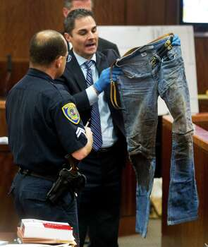 Prosecutor John Jordan holds up a pair of bloody jeans as Houston police senior officer Chris Duncan testifies during the trial against Ana Lilia Trujillo  on Tuesday, April 1, 2014, in Houston. Photo: Brett Coomer, Houston Chronicle / © 2014 Houston Chronicle
