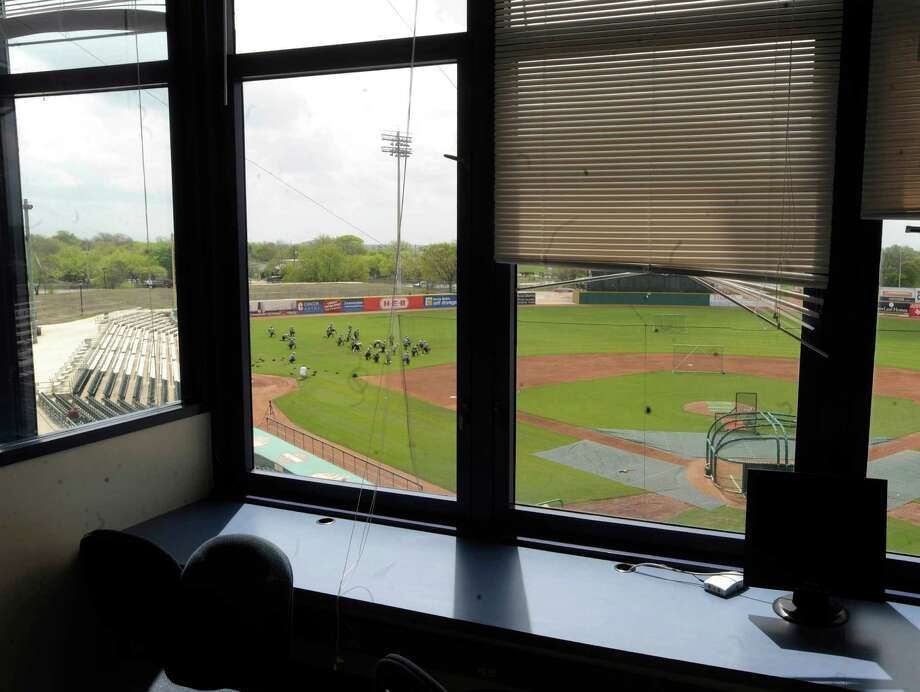 Members of the San Antonio Missions baseball team stretch before their workout at Wolff Stadium, as seen through a press box window on Tuesday, April 1, 2014. Photo: Billy Calzada, San Antonio Express-News / San Antonio Express-News