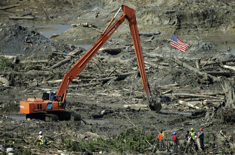 Using equipment like a long-arm excavator to reach watery areas, workers continue to search for victims of the deadly mudslide that hit the community of Oso, Wash., on March 22. Photo: Ted S. Warren / Associated Press / AP