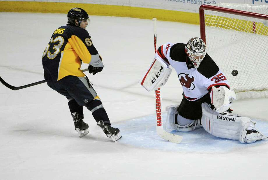 Buffalo Sabres center Tyler Ennis (63) scores on New Jersey Devils goaltender Cory Schneider (35) during the team shootout of an NHL hockey game in Buffalo, N.Y., Tuesday, April 1, 2014.  Buffalo won 3-2. (AP Photo/Gary Wiepert) ORG XMIT: NYGW105 Photo: Gary Wiepert / FR170498 AP