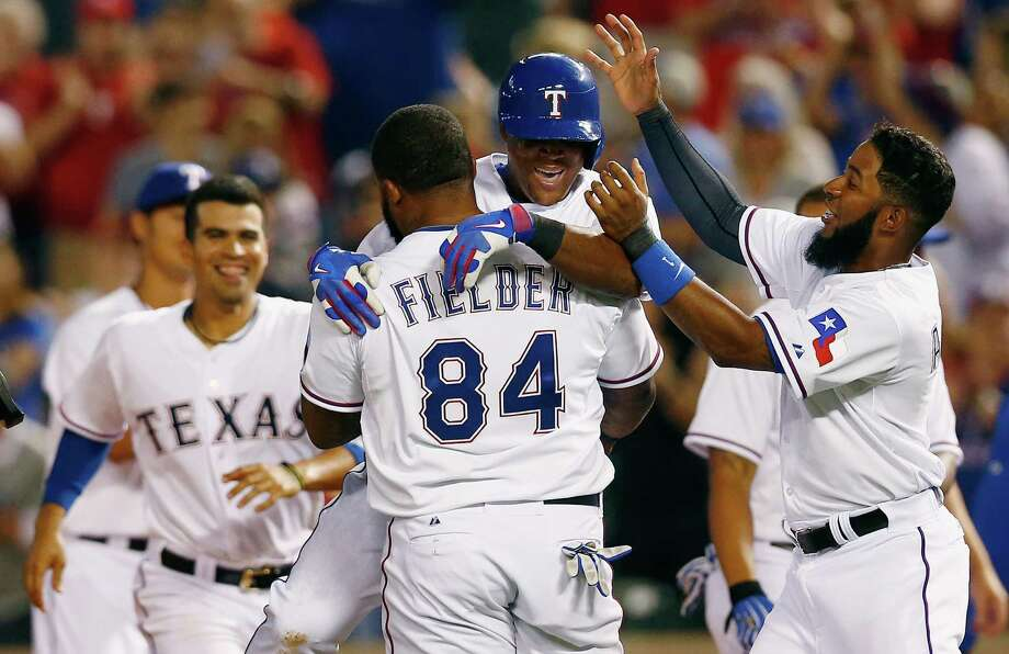 ARLINGTON, TX - APRIL 01:  Adrian Beltre #29 of the Texas Rangers celebrates with Prince Fielder #84 of the Texas Rangers and Elvis Andrus #1 of the Texas Rangers after hitting the game winning RBI against the Philadelphia Phillies in the bottom of the ninth inning at Globe Life Park in Arlington on April 1, 2014 in Arlington, Texas. Photo: Tom Pennington, Getty Images / 2014 Getty Images