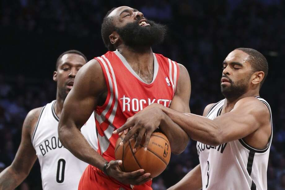 Alan Anderson of the Nets ties up Rockets shooting guard James Harden. Photo: John Minchillo, Associated Press