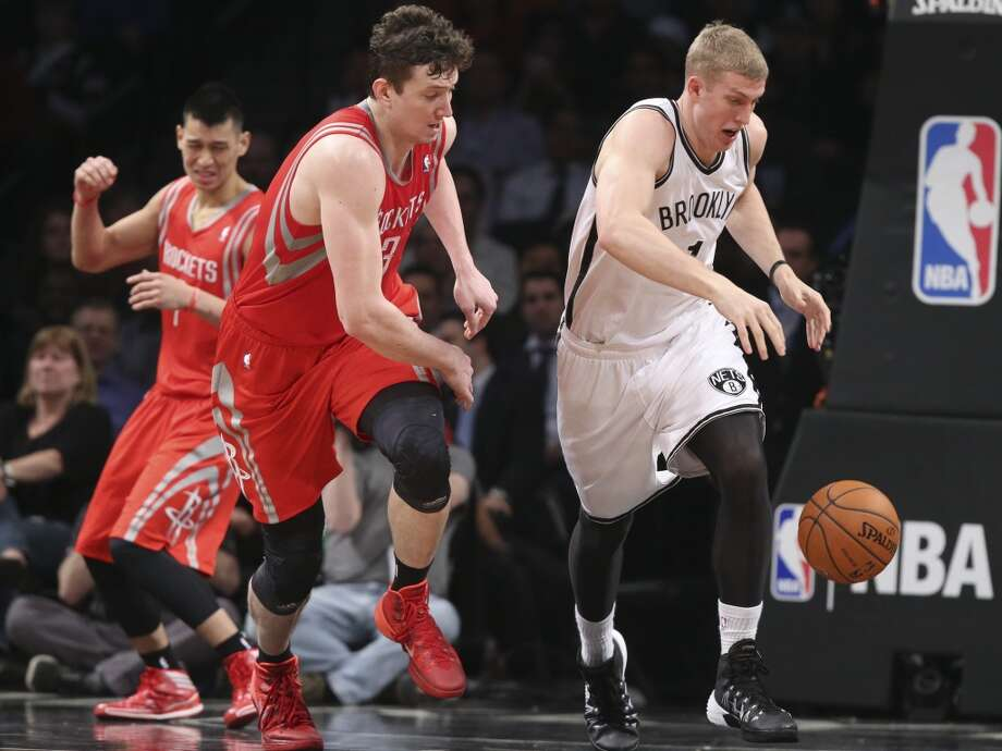Rockets center Omer Asik is outrebounded by Mason Plumlee of the Nets. Photo: John Minchillo, Associated Press