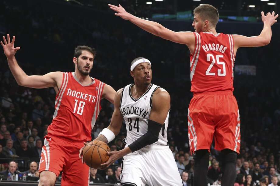 Paul Pierce of the Nets looks to pass as Rockets forward Omri Casspi and Chandler Parsons defend. Photo: John Minchillo, Associated Press