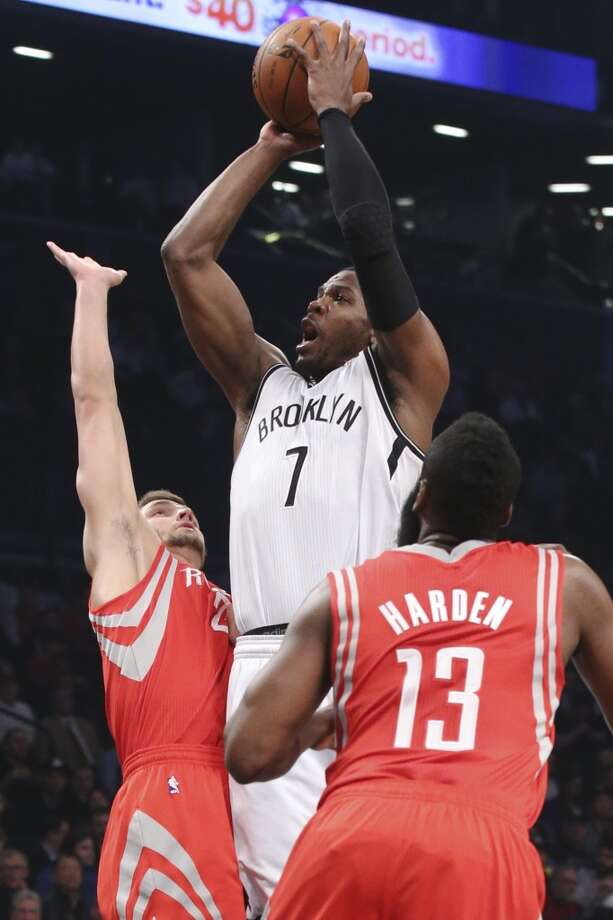 Joe Johnson of the Nets shoots over Chandler Parsons and James Harden of the Rockets. Photo: John Minchillo, Associated Press