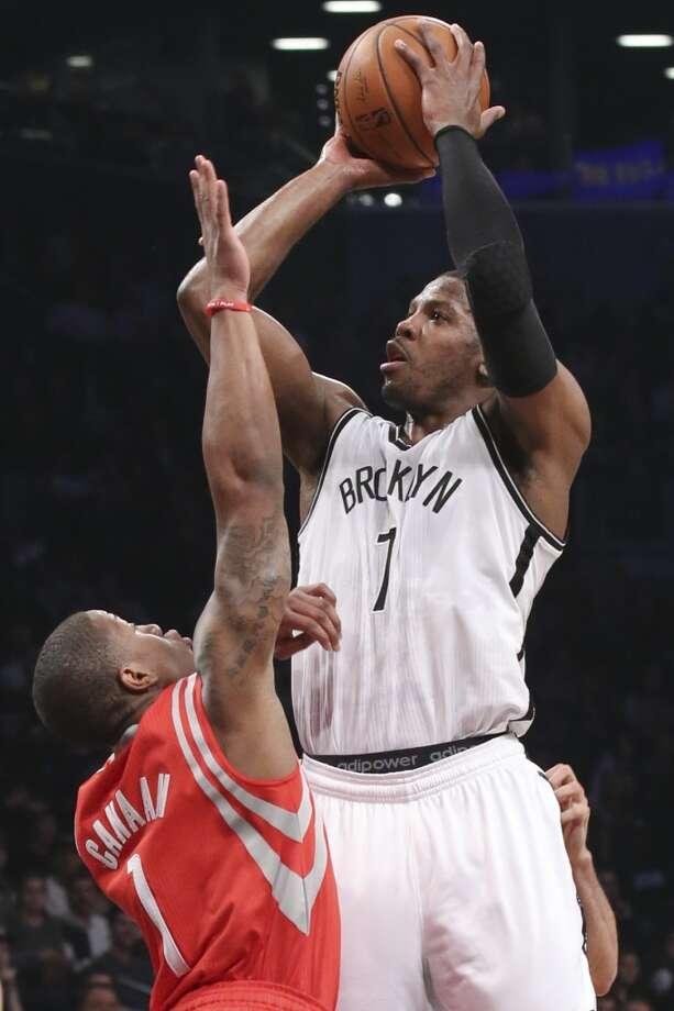 Joe Johnson of the Nets shoots over Isaiah Canaan of the Rockets. Photo: John Minchillo, Associated Press
