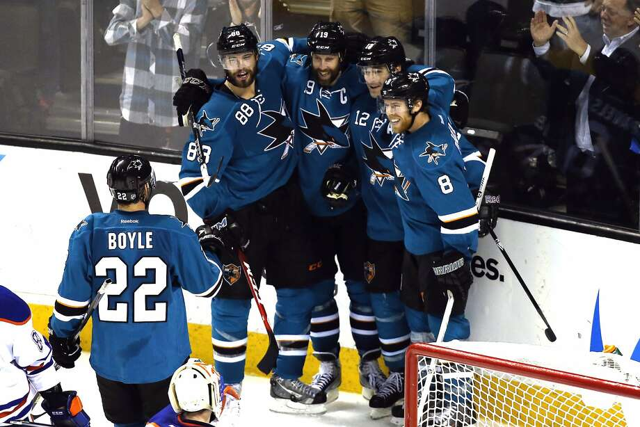The Sharks' Patrick Marleau (12) is congratulated by Brent Burns (88), Joe Thornton (19) and Joe Pavelski (8) after his late goal. Photo: Robert Stanton, Reuters
