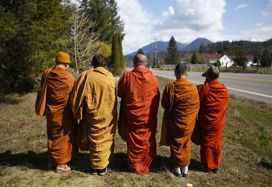 Buddhist monks from the Atammayatarama Buddhist Monastery in Woodinville chant for the victims of a deadly mudslide near a west side road block, Tuesday, April 1, 2014, in Oso, Wash. (AP Photo/The Herald, Sofia Jaramillo) Photo: Sofia Jaramillo, Associated Press