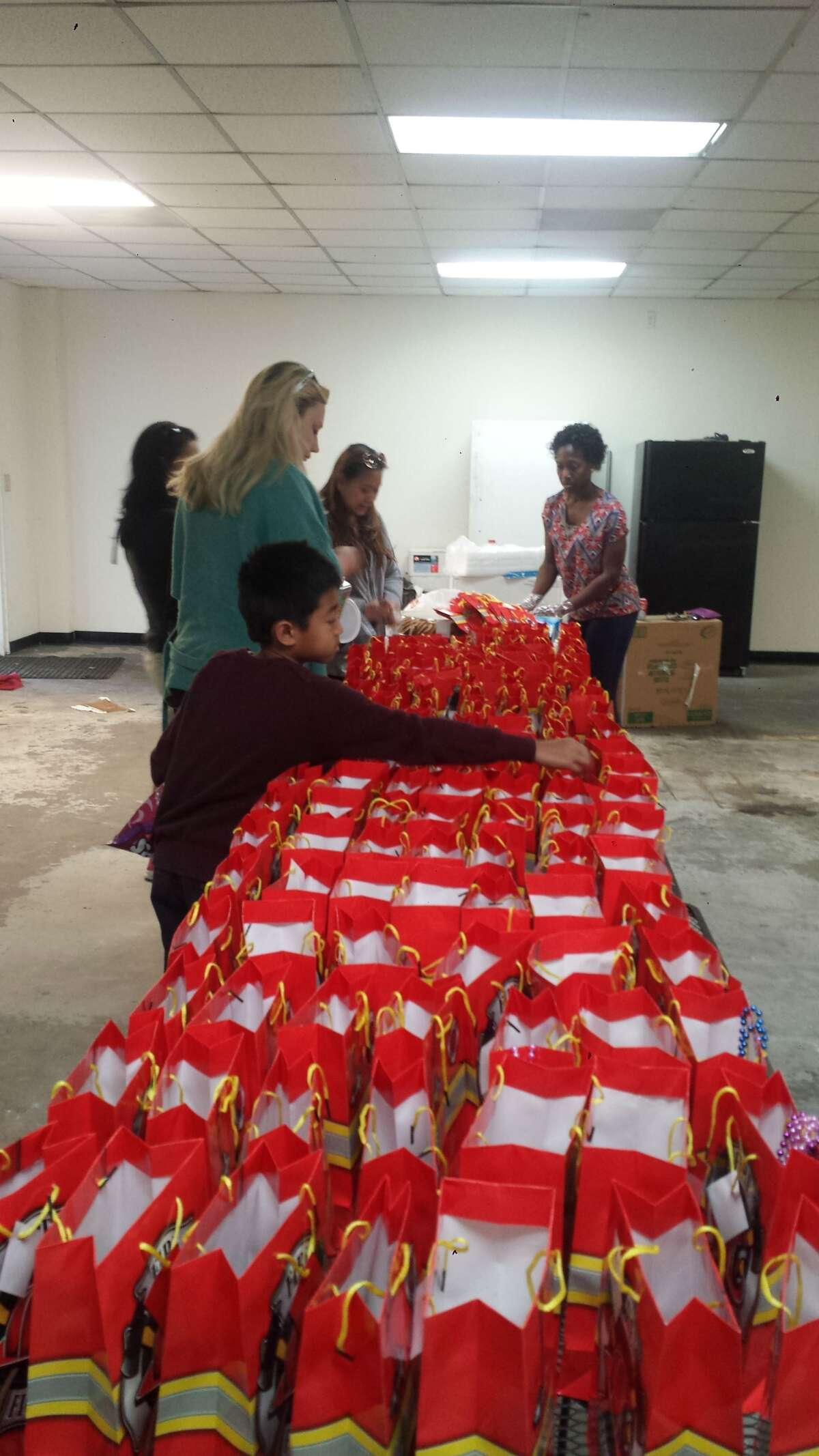 Dylan Carnley, foreground, helps pack treat bags for Houston firefighters. Courtesy photo