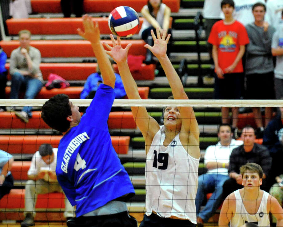 Staples' Lucas Grevers looks to block a spike by Glastonbury's Calvin Haught, during Class L volleyball finals action in Shelton, Conn. on Friday June 7, 2013. Photo: Christian Abraham / Connecticut Post