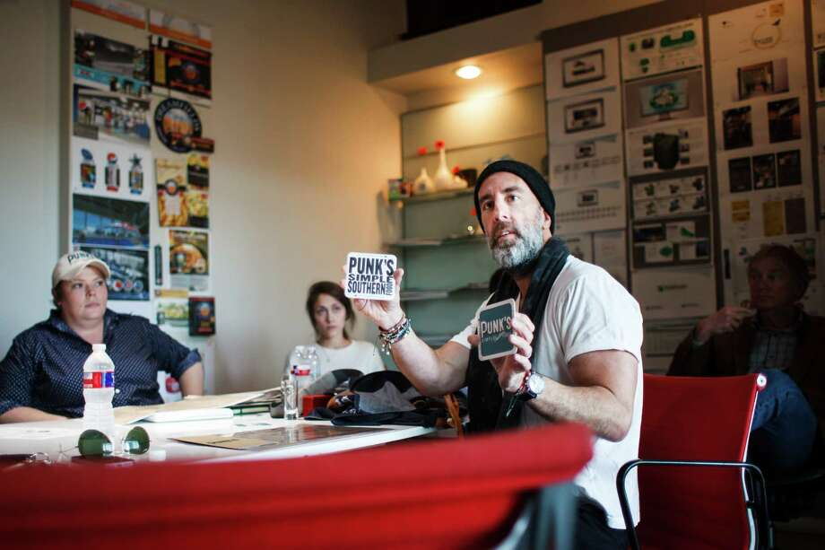 Grant Cooper, center, holds coasters his new restaurant Punk's Simple Southern Food during a meeting at Acumen Design, Wednesday, March 12, 2014, in Houston.  Clark Cooper Concepts, owners Grant Cooper and Charles Clark, are already responsible for several restaurants: Ibiza, Brasserie 19, Coppa, Coppa Osteria and Punk's Simple Southern Food.  ( Michael Paulsen / Houston Chronicle ) Photo: Michael Paulsen, Staff / © 2014 Houston Chronicle