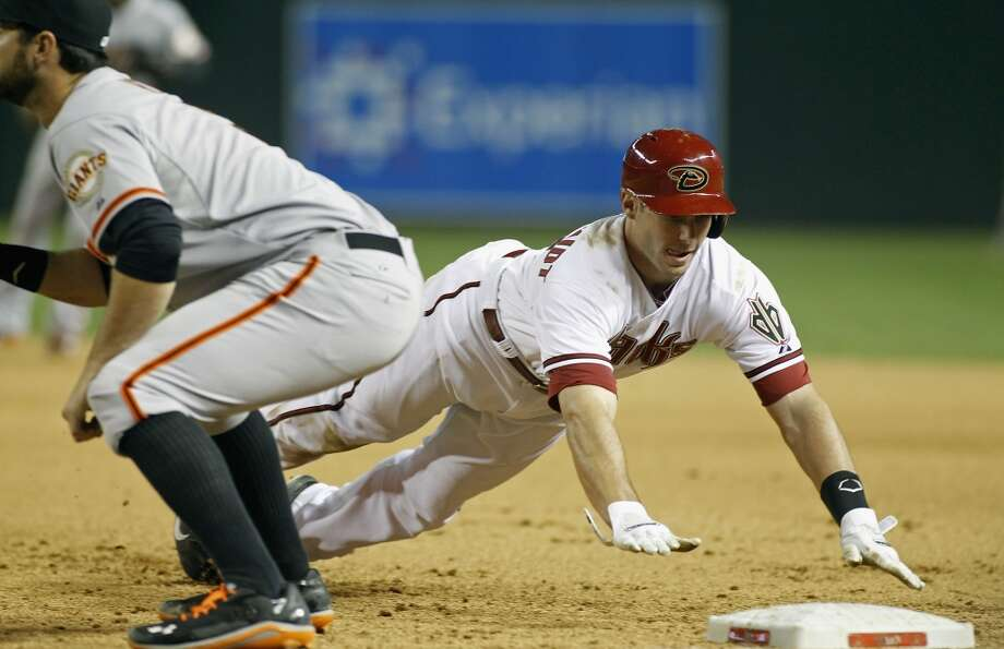 Paul Goldschmidt #44 of the Arizona Diamondbacks dives back to first base safely as Brandon Belt #9 of the San Francisco Giants waits on the throw during the seventh inning of a MLB game at Chase Field on April 1, 2014 in Phoenix, Arizona. Photo: Ralph Freso, Getty Images