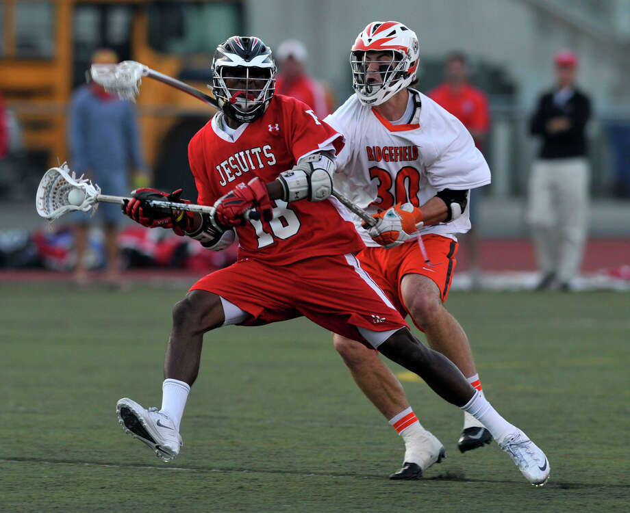 Fairfield Prep's Austin Sims is pressured from behind by Ridgefield's Sam Gravitte during their Division L semifinal game at Brien McMahon High School in Norwalk on Wednesday, June 5, 2013. Fairfield Prep won, 12-9. Photo: Jason Rearick / Stamford Advocate