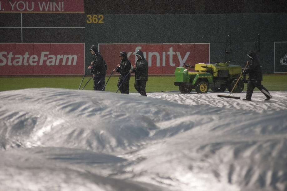 Members of the Oakland Athletics field crew sweep rain off the tarp after the game against the Cleveland Indians was postponed due to rain. Photo: Ed Szczepanski, Reuters