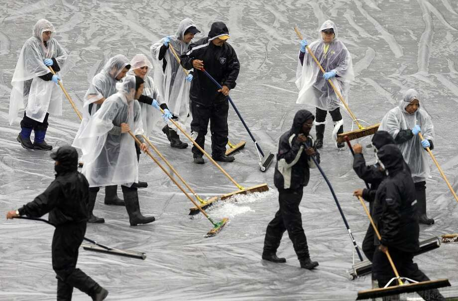 Workers clear water off a tarp covering the infield prior to a baseball game between the Cleveland Indians and the Oakland Athletics on Tuesday, April 1, 2014, in Oakland, Calif. (AP Photo/Ben Margot) Photo: Ben Margot, Associated Press